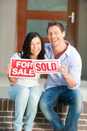 Happy couple holding for sale and sold signs in front of a new house